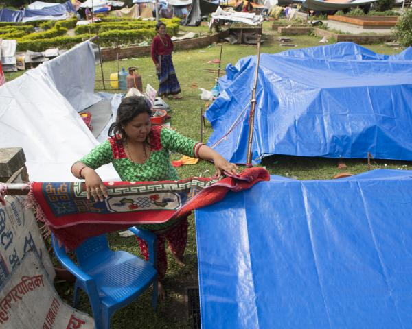 a-woman-sets-up-her-tent-in-lalitpur-nepal.